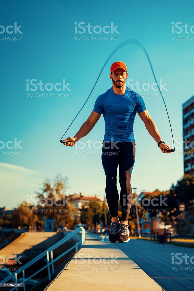 Young male athlete skipping rope stock photo