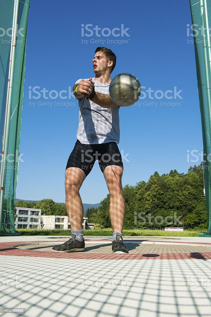 Young male athlete throwing the hammer stock photo