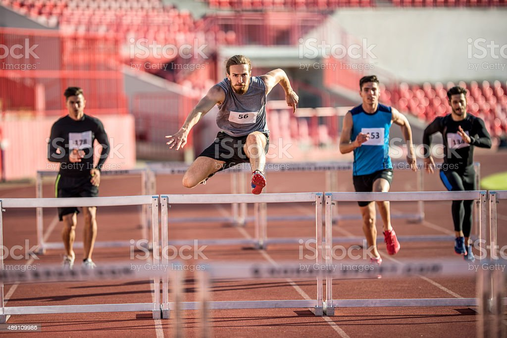 Young male athletes jumping hurdles on a sports race. stock photo