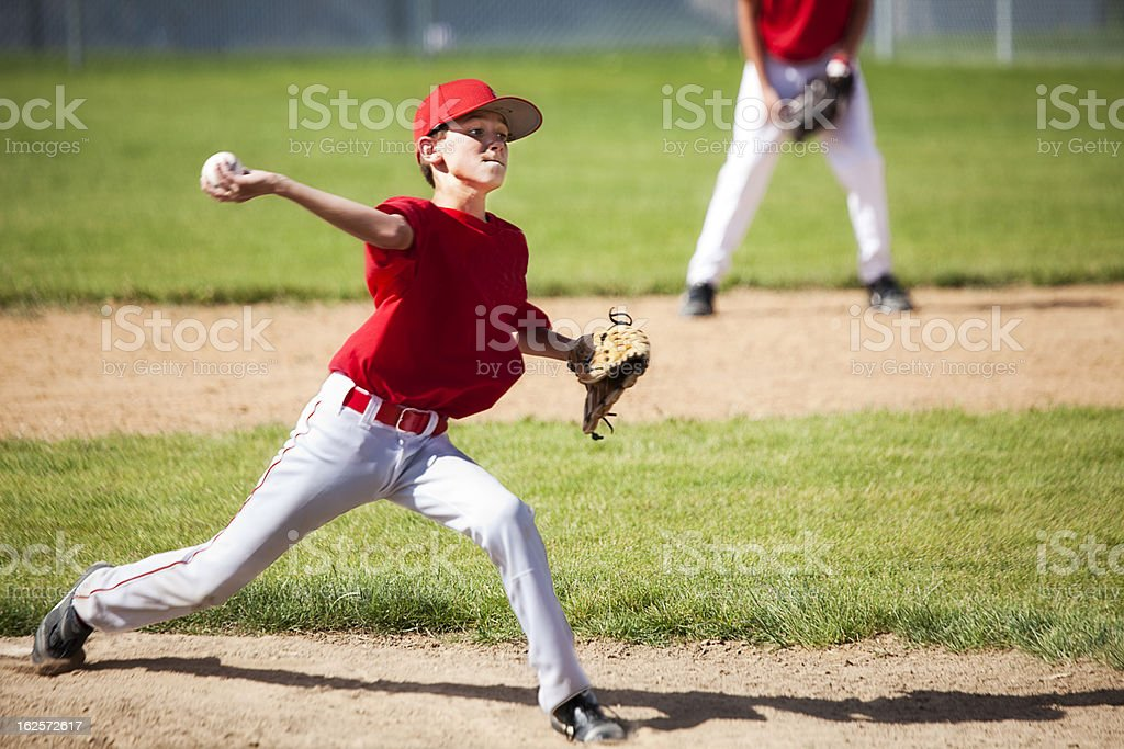 Young Male Baseball Pitcher Powers through Delivery stock photo
