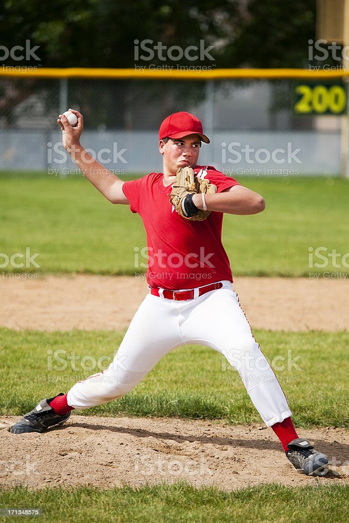 Young Male Baseball Pitcher Stretches on Pitcher's Mound stock photo