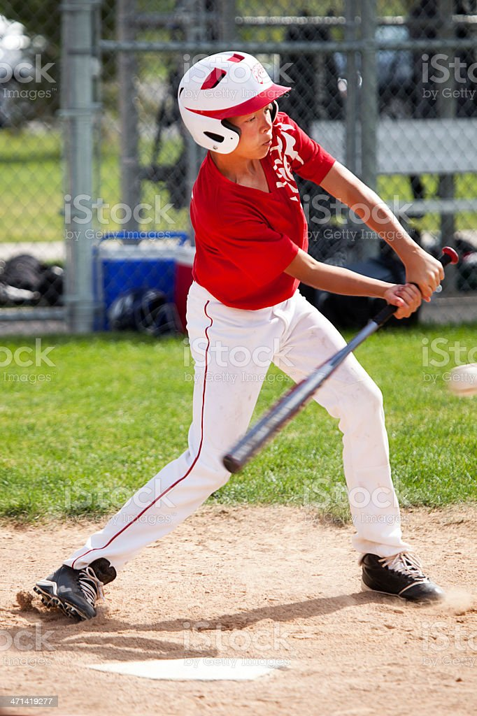 Young Male Baseball Player Hits Ball in Batter's Box stock photo