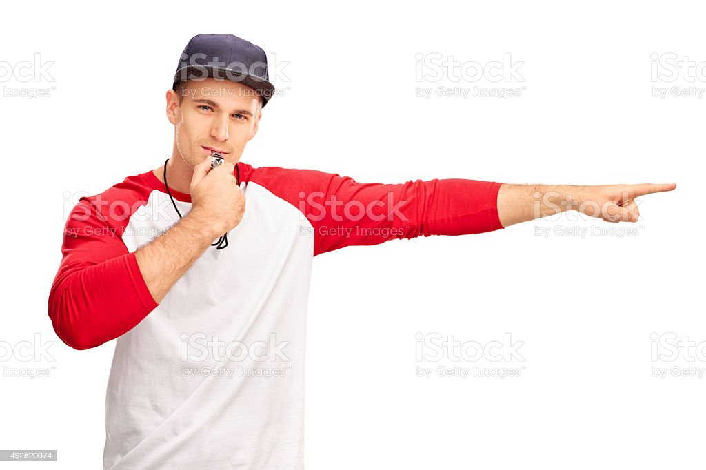Young male baseball referee blowing a whistle stock photo
