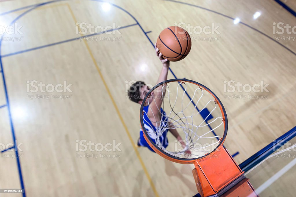 Young male basketball player attempting a dunk stock photo