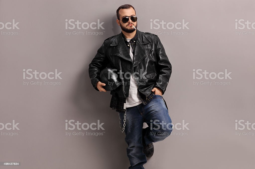Young male biker leaning against a wall stock photo