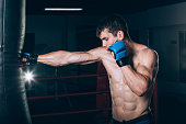 Young Male boxer using a punching bag in gym.
