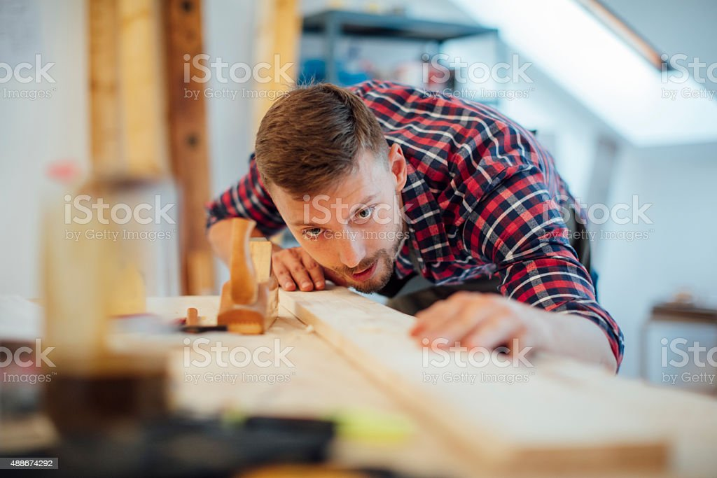 Young Male carpenter working on a project in his workshop. stock photo