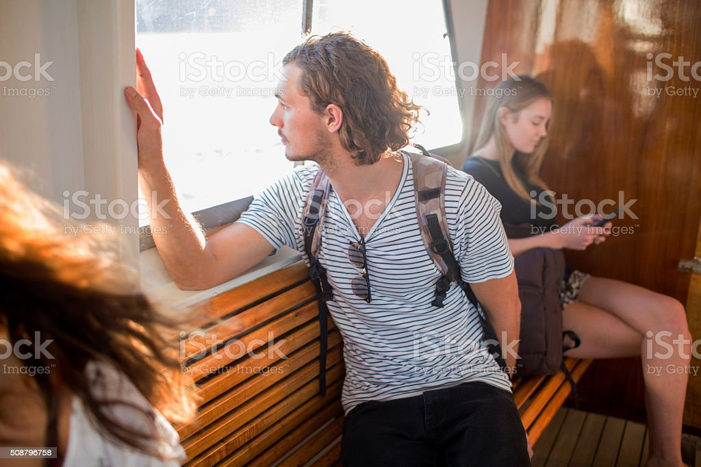 Young male communting on passenger ferry looking out window stock photo