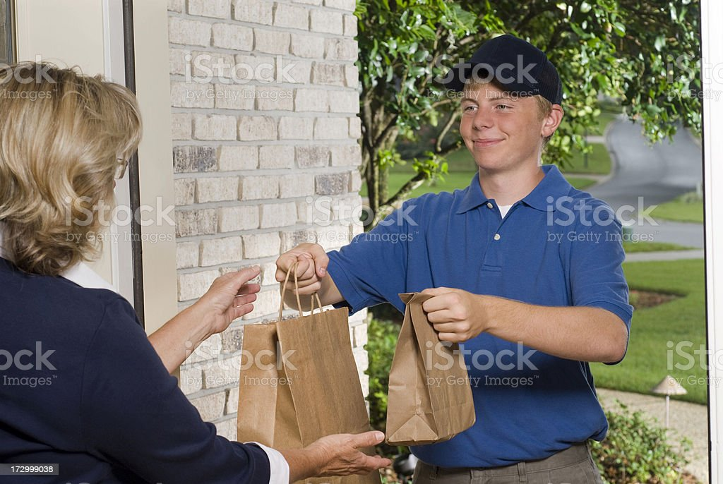 young male delivers fast food to woman stock photo