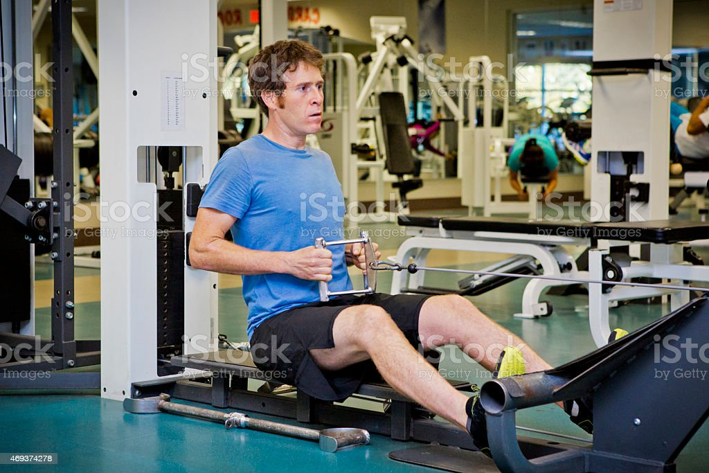 Young male doing weight lifting in gym. stock photo