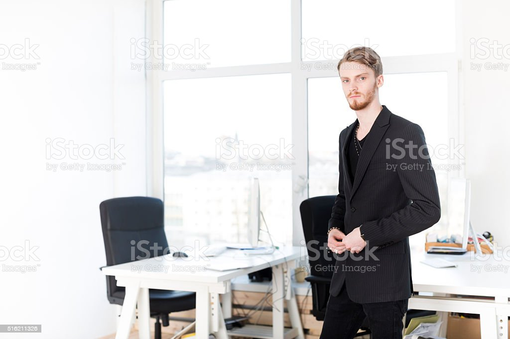 Young Male Entrepreneur Buttoning His Jacket In Office stock photo