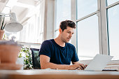 Young male executive working on laptop
