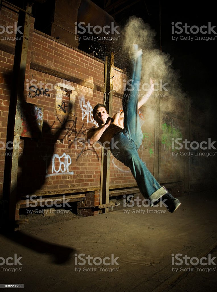 Young Male Fighter Doing Flying Kicks at Night stock photo