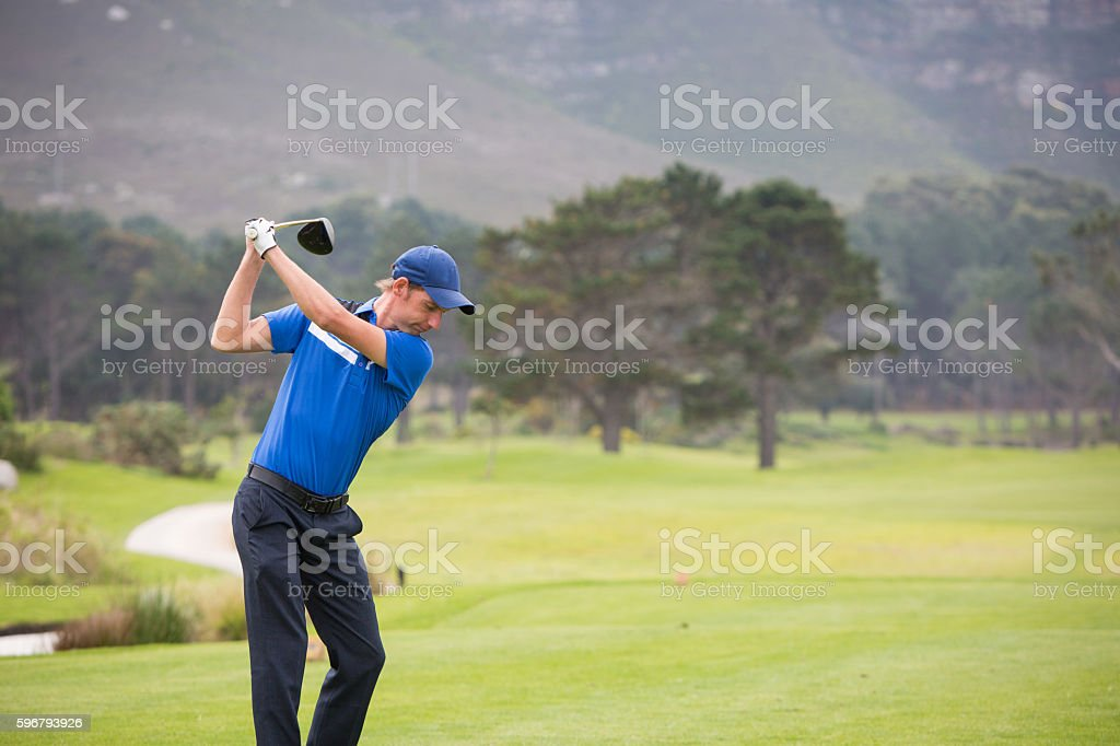 Young male golfer hitting his t-shot stock photo