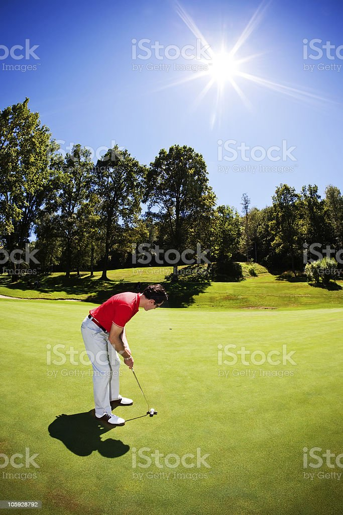 Young male golfer in red shirt putting ball stock photo
