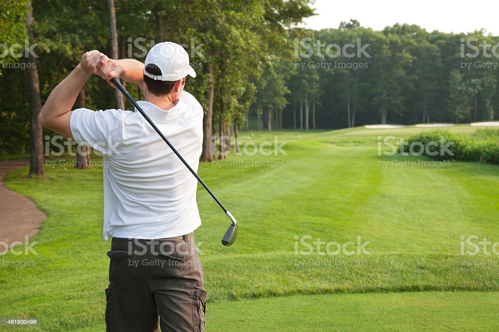 Young male golfer tees off on a par three stock photo