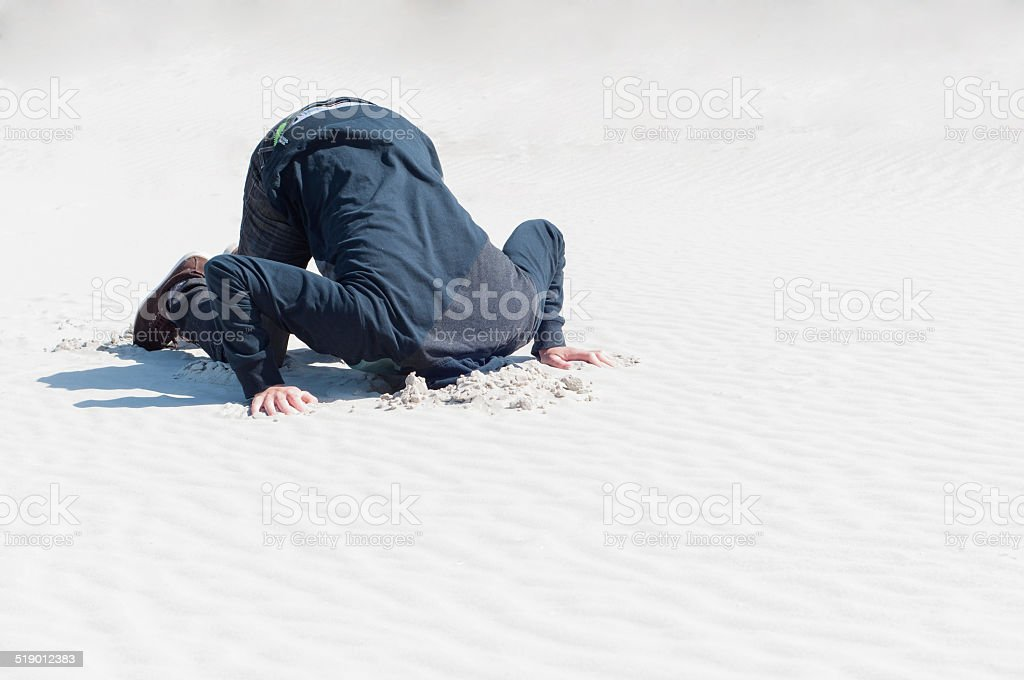 Young male hiding head in sand stock photo