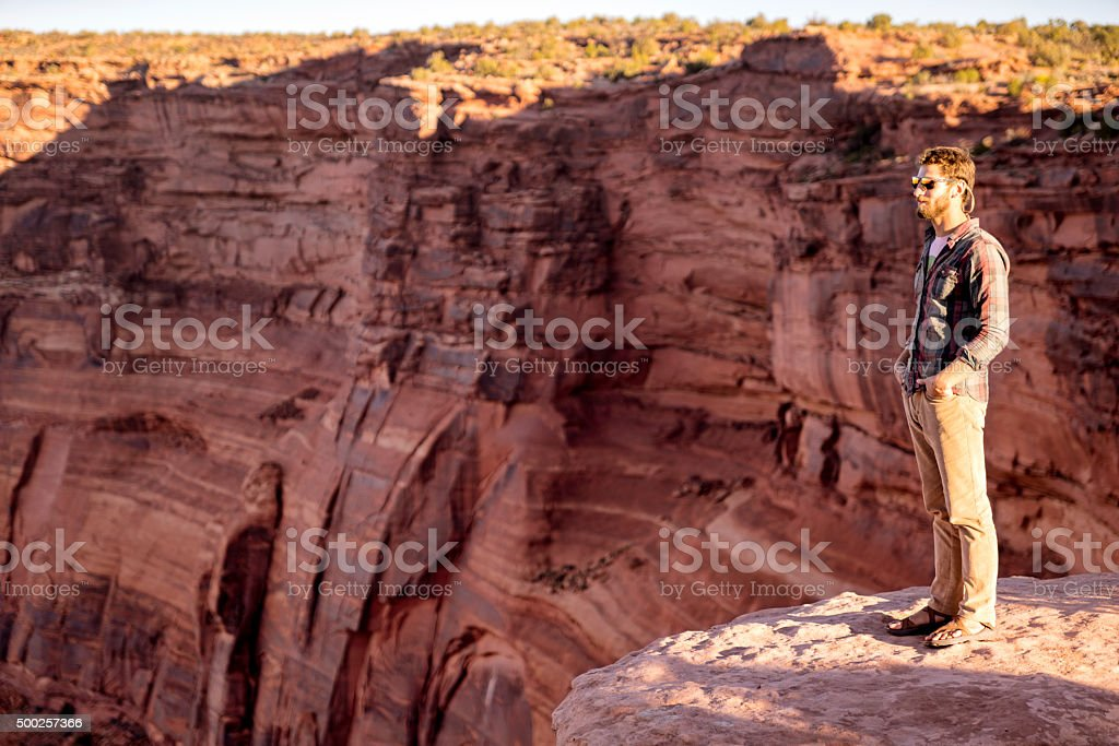 Young Male Hiker Standing on top of a Cliff stock photo