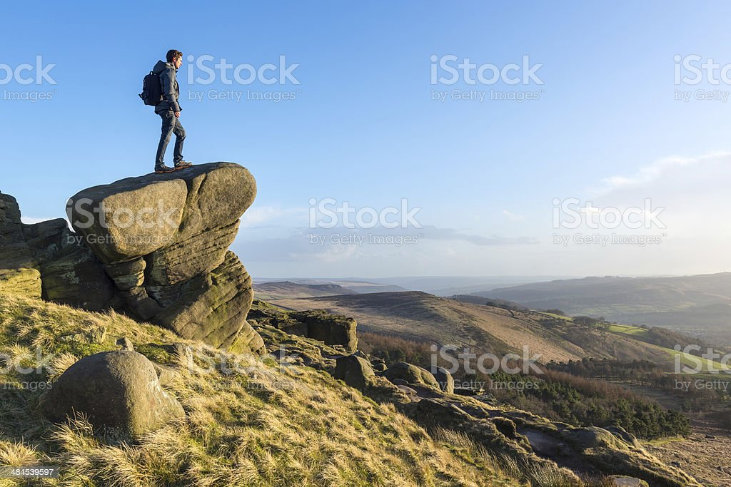 Young male hiker stood on rocky outcrop stock photo