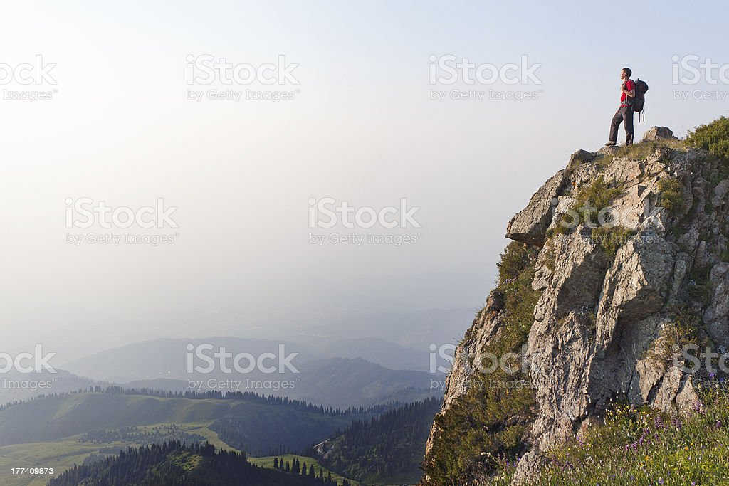 Young male hiker with backpack standing on top edge of cliff stock photo