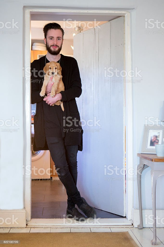 Young Male Holding A Puppy stock photo