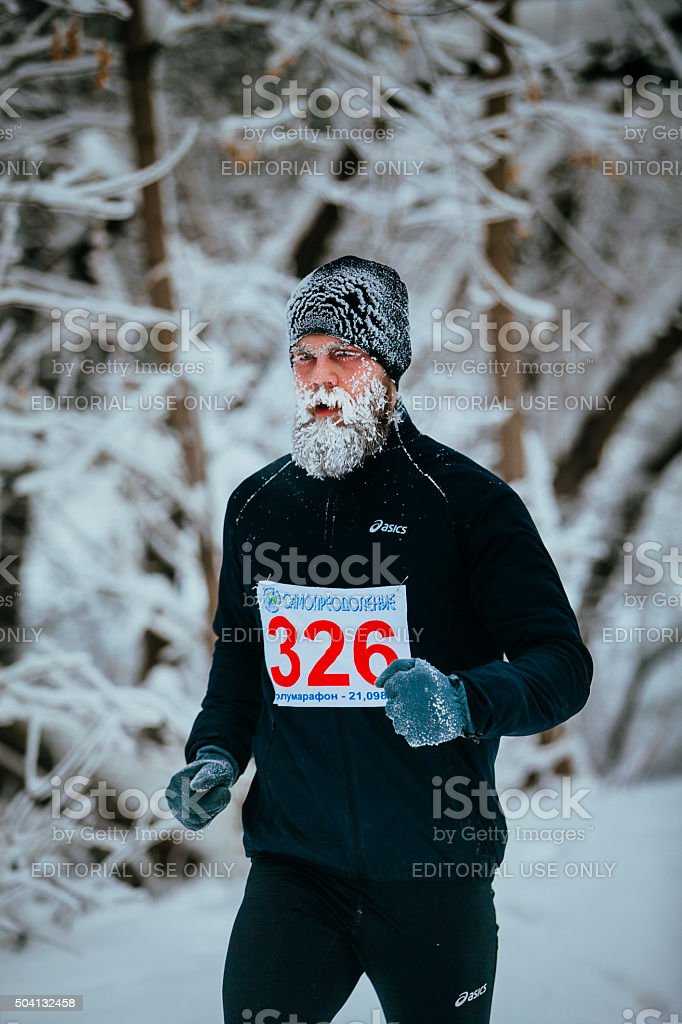 young male jogger running through a snowy Park alley stock photo