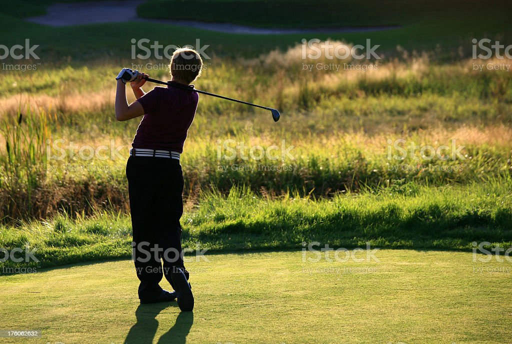 Young Male Junior Level Golfer Swinging Fairway Metal stock photo