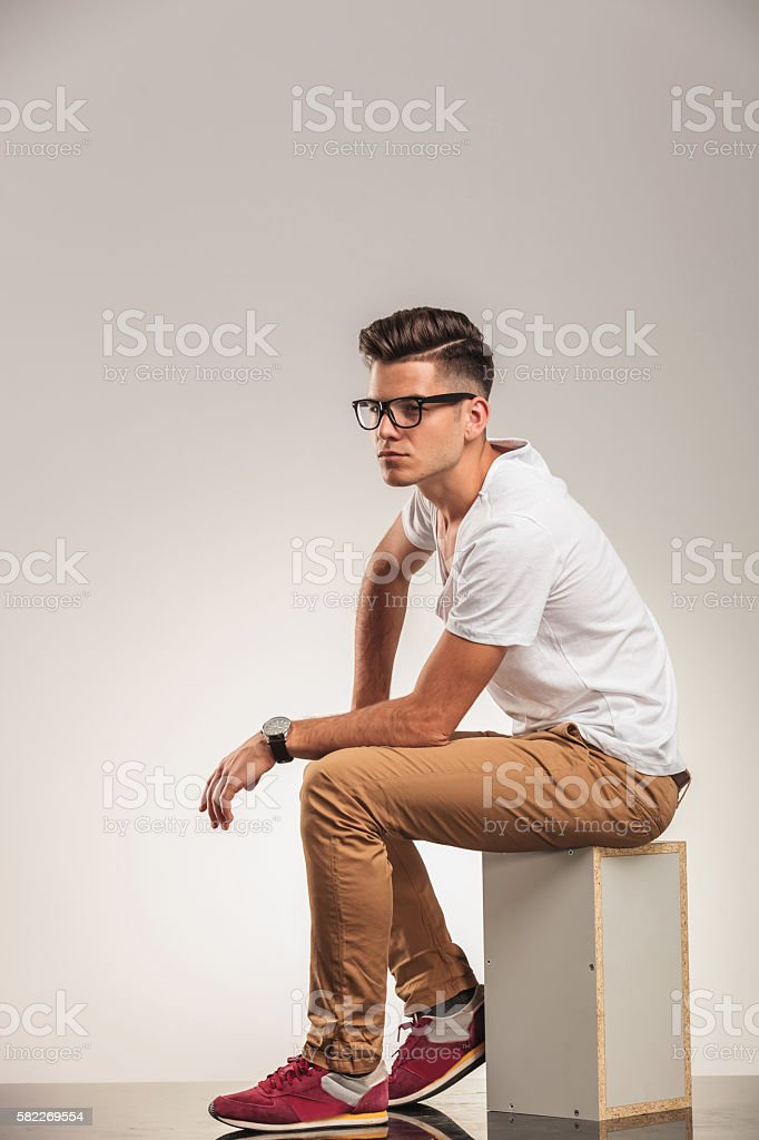 young male looking away while seated stock photo