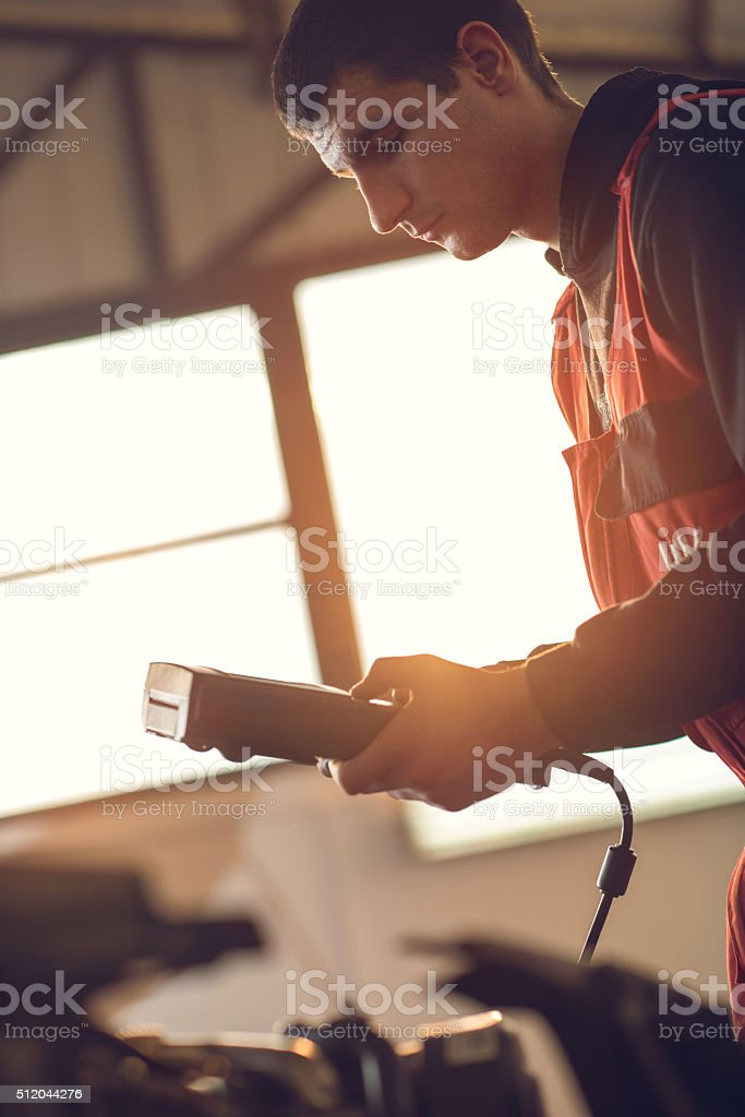 Young male mechanic using voltmeter in a repair shop. stock photo