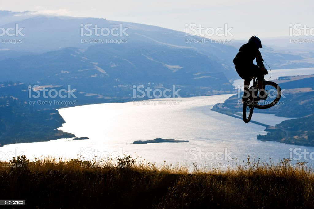 A young male mountain bike rider hits a jump on a downhill trail on a sunny day. stock photo