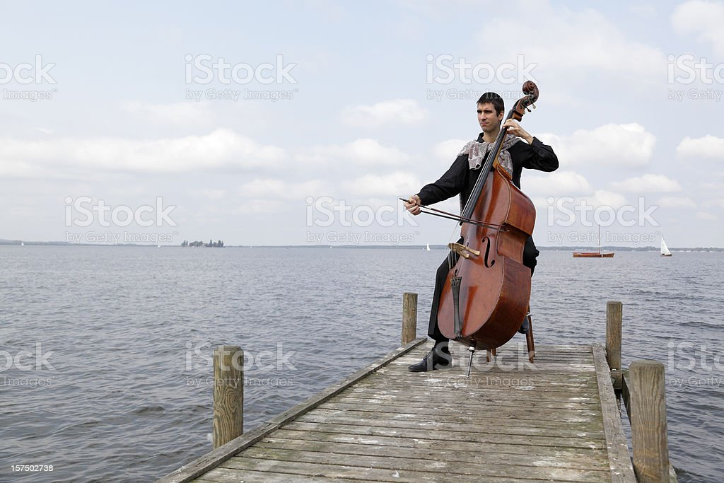Young male musician playing double bass on lakeside jetty (XXXL) stock photo