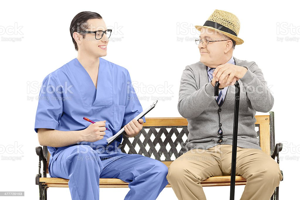 Young male nurse talking to senior gentleman seated on bench stock photo