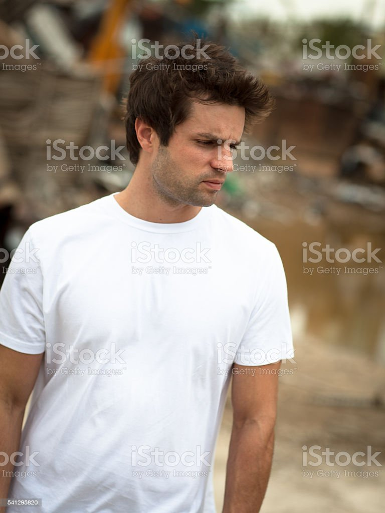 Young male outdoors wearing white t-shirt looking down stock photo