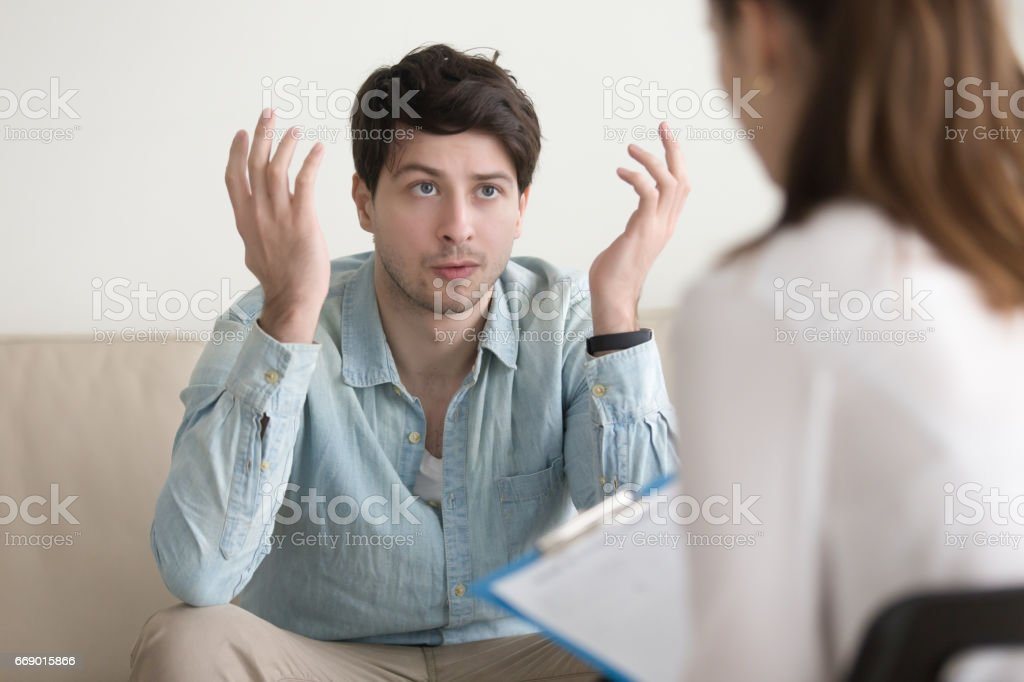 Young male patient talking about his problem to female psychotherapist stock photo