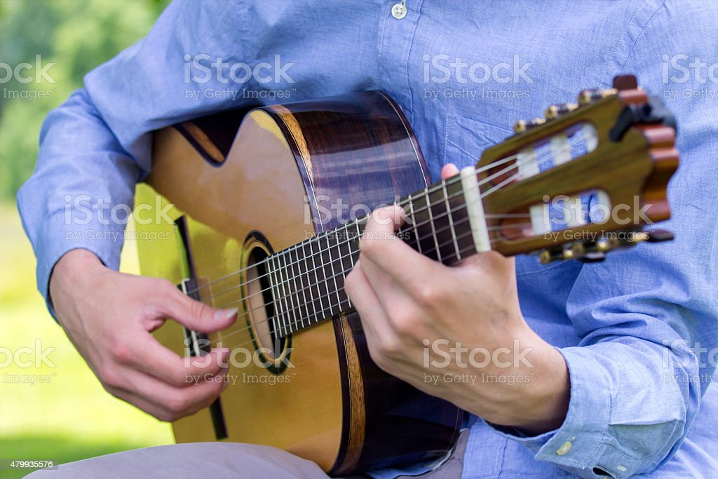 Young male playing a classic guitar outside stock photo