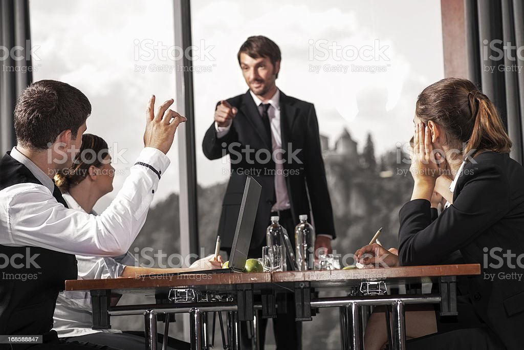 Young Male Professional Raising Hand During a Meeting royalty-free stock photo