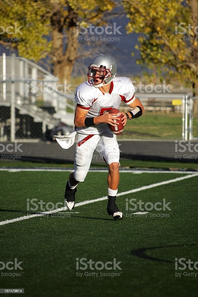 Young Male Quarterback Rolling Out Left with Football stock photo