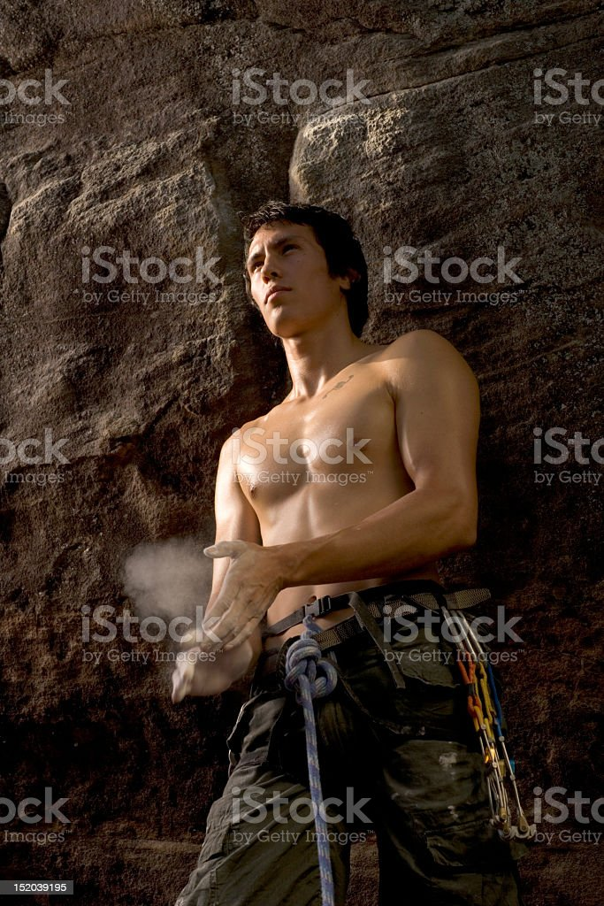 Young male rock climber chalking hands by rock face royalty-free stock photo