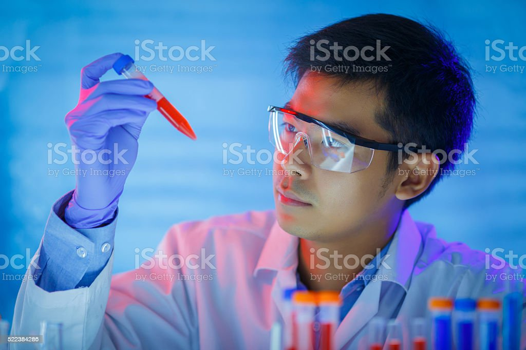 young male scientist holding test tube with blood sample stock photo