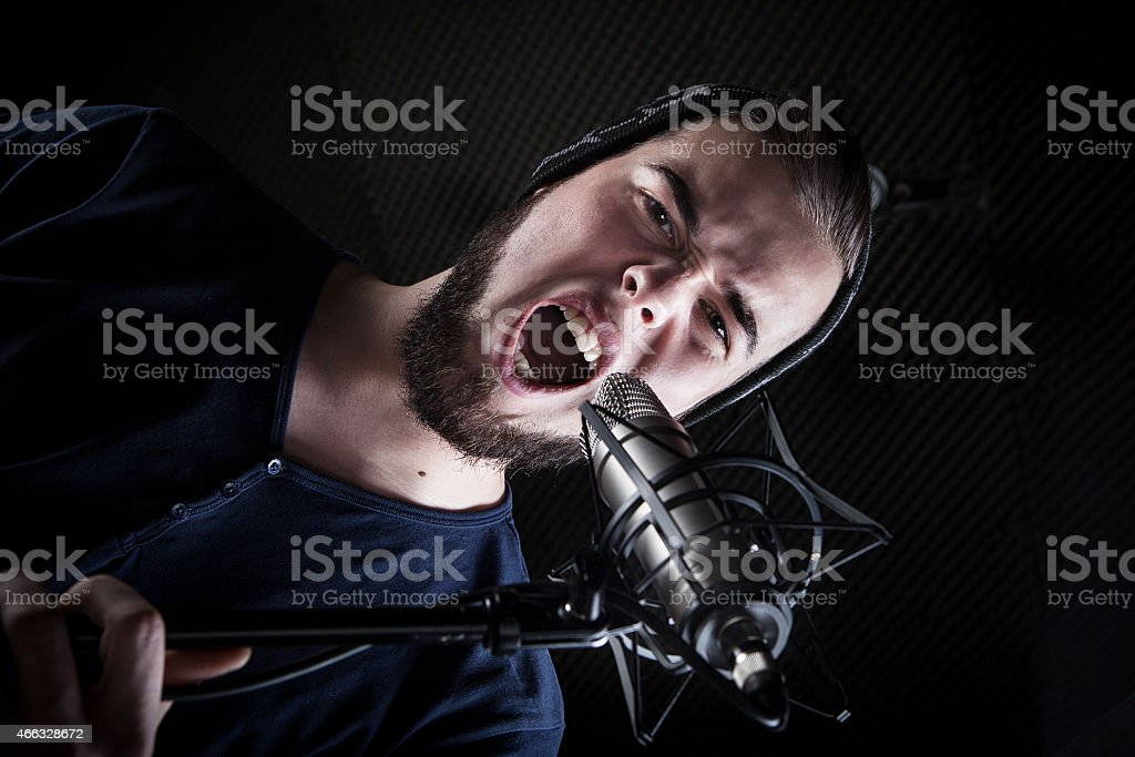 Young male singer at the sound recording studio, shouting into the...