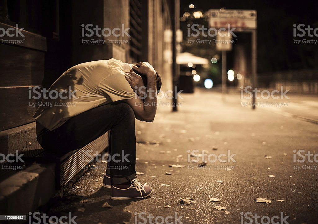 Young male sitting on stairs alone on the street stock photo