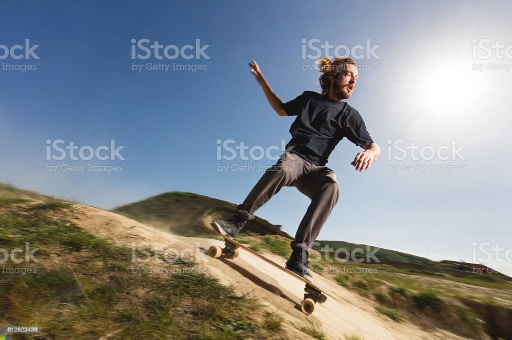 Young male skateboarder going downhill in blurred motion. stock photo