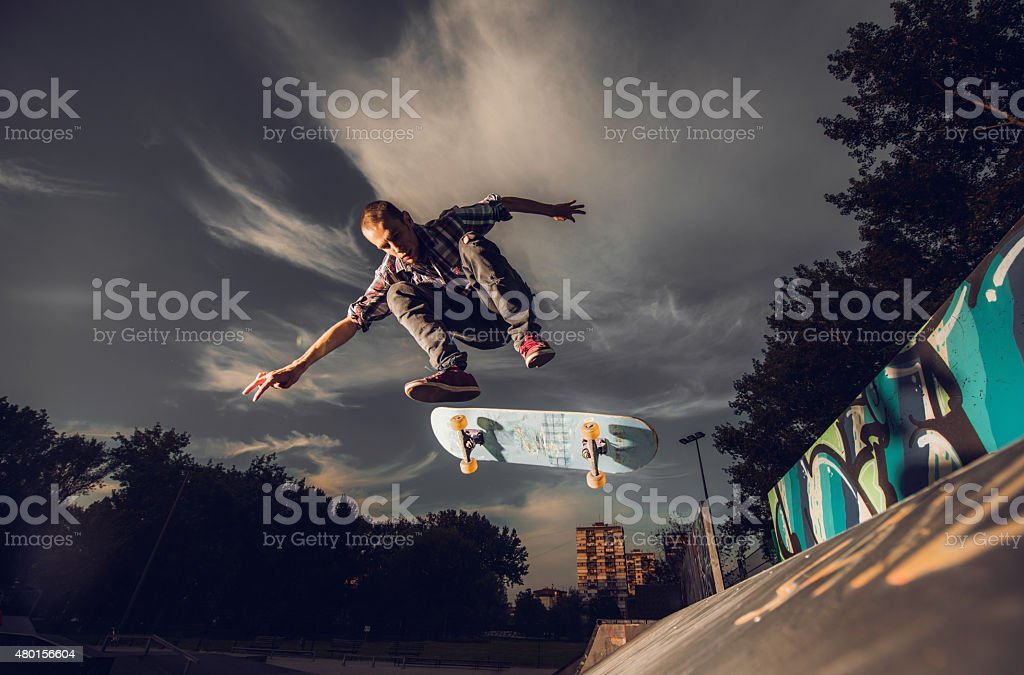Young male skateboarder in action against the sky. stock photo