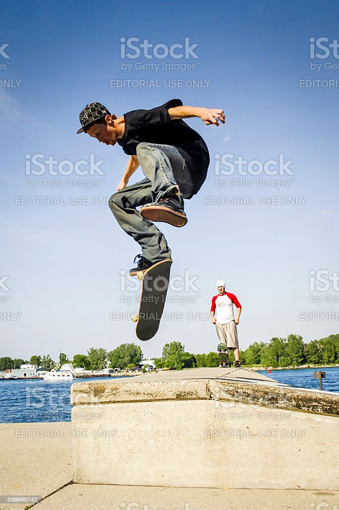 Young male Skateboarders practice jump tricks and maneouvers stock photo