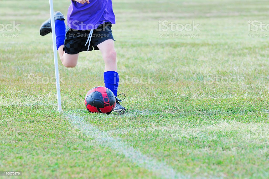 Young Male Soccer Player Making a Corner Kick with Ball stock photo