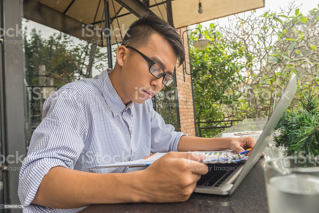 Young male student doing assignment homework with laptop at outdoor stock photo