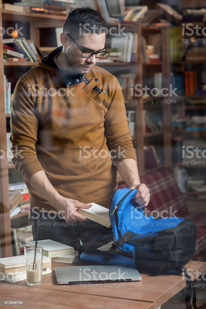 Young male student packing books into his backpack. stock photo