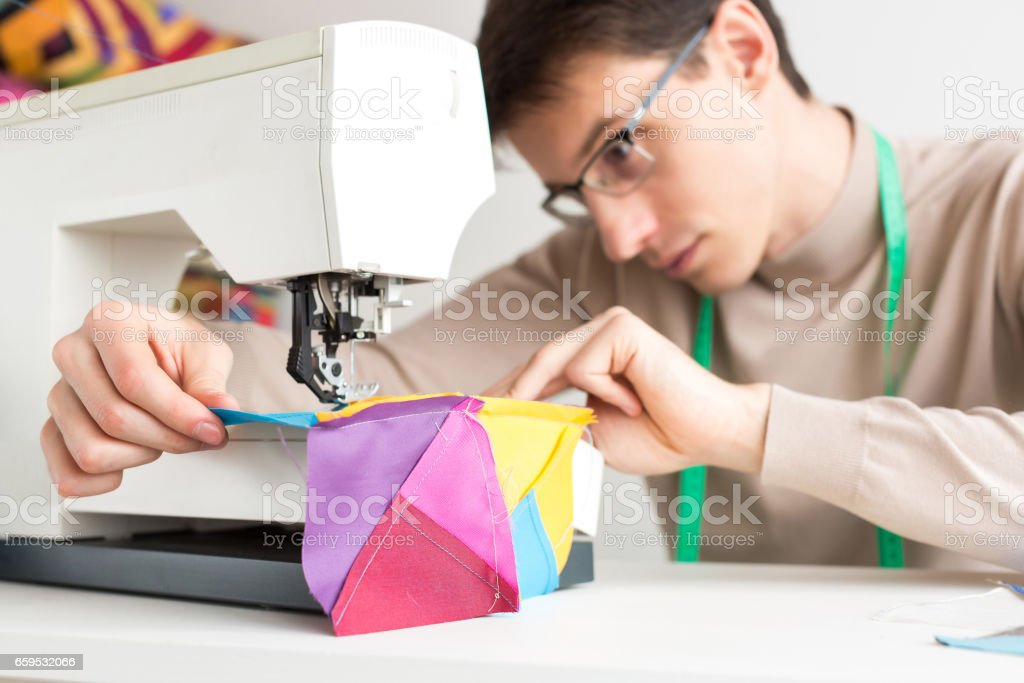 young male tailor in the table works on the sewing machine and stitch designer patchwork from pieces of colored cloth stock photo