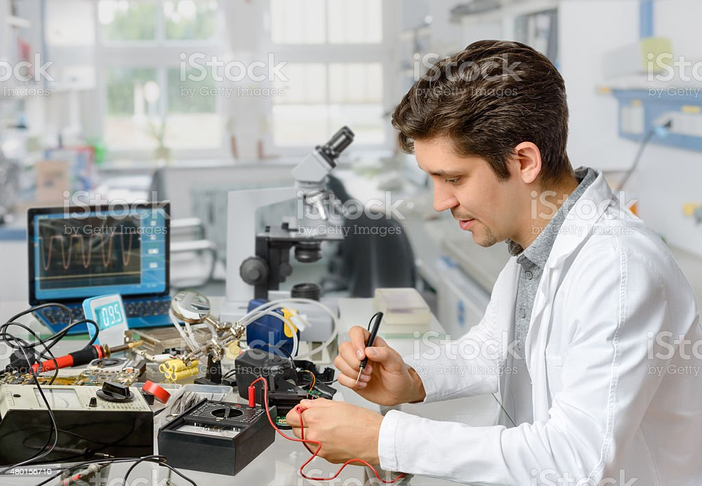 Young male tech or engineer repairs electronic equipment in rese stock photo
