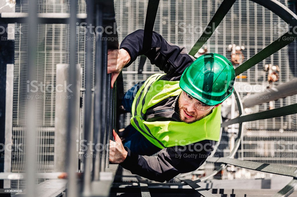 Young male technician climbing ladder in industry stock photo
